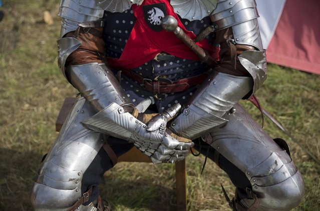 A historical re-enactor in a living history camp prepares his costume as he takes part in an anniversary event for the Battle of Bosworth near Market Bosworth in central Britain August 22, 2015. (Photo by Neil Hall/Reuters)