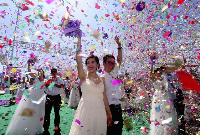 Couples celebrate during a mass wedding ceremony to mark the Qixi Festival in Shenyang, Liaoning province August 2, 2014. According to local media, 77 couples attended the mass wedding on Saturday. Qixi, also known as the Double Seventh Festival and the Chinese version of Valentine's Day, falls on the seventh day of the seventh month in the Chinese lunar calendar. (Photo by Reuters/Stringer)