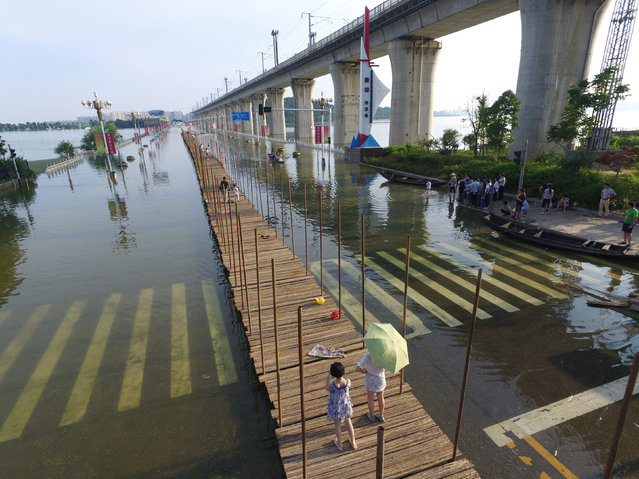 People walk on a bridge under construction at a flooded area in Wuhan, Hubei Province, China, July 9, 2016. (Photo by Reuters/Stringer)