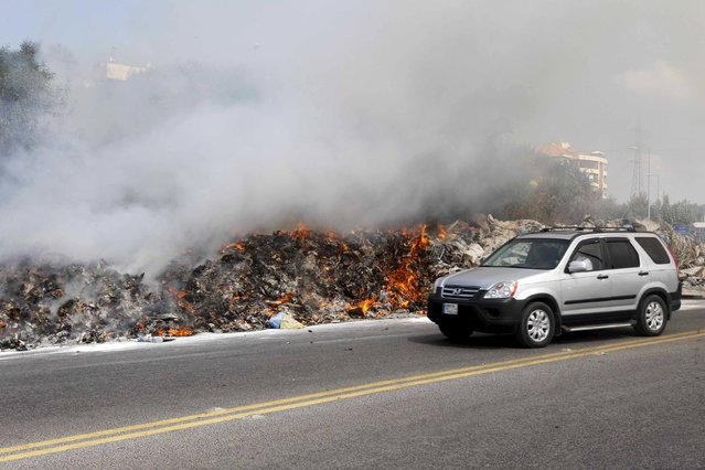 A car drives past burning garbage set on fire by residents, in Baabda near Beirut, Lebanon August 24, 2015. (Photo by Mohamed Azakir/Reuters)