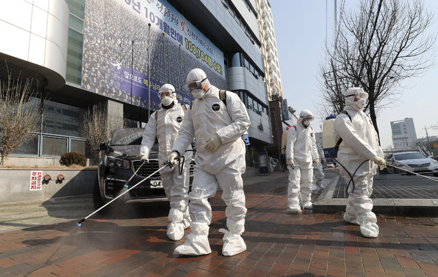Workers wearing protective gears spray disinfectant against the new coronavirus in front of a church in Daegu, South Korea, Thursday, February 20, 2020. The mayor of the South Korean city of Daegu urged its 2.5 million people on Thursday to refrain from going outside as cases of the new virus spike. (Photo by Kim Jong-un/Yonhap via AP Photo)