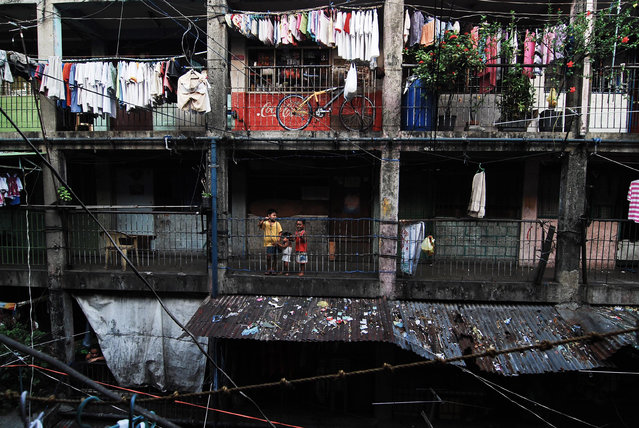 Children play in dilapidated housing, where their community resides, on August 11, 2014 in Manila, Philippines. (Photo by Dondi Tawatao/Getty Images)