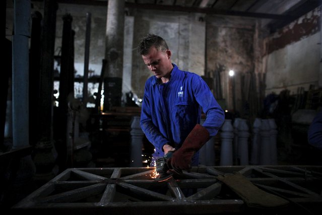 Jorge Fajardo, 24, welds a fence in a small factory in downtown Havana, April 16, 2015. (Photo by Alexandre Meneghini/Reuters)