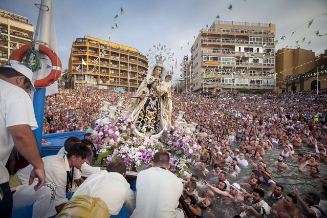 Penitents carry a statue of the Virgen del Carmen, the patron saint of fishermen, onto a boat at the Puerto de la Cruz on the Spanish Canary island of Tenerife on July 12, 2014. Every year, local residents of the resort carry the statue of the Virgin from its chapel to a small beach in the fishing habour. Once at the beach, the fishermen put the statue on board a decorated boat and the statue sails along the coast. (Photo by Desiree Martin/AFP Photo)
