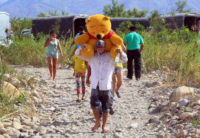 """Colombian nationals carry their belongings across the Tachira river, from Venezuela to the La Parada area, close to Cucuta, Colombia, 25 August 2015. Colombian President Juan Manuel Santos asked the Venezuelan authorities to respect the Colombian people living in the border area and considered as """"unacceptable"""" and """"unbearable"""" the method used to deport them from Venezuelan territory. (Photo by Mauricio Duenas Castaneda/EPA)"""