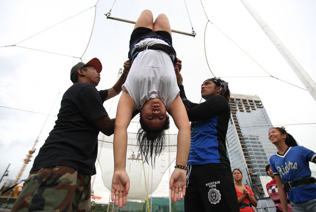 In this photo taken Tuesday, August 12, 2014, flying trapeze instructors teaches techniques to students during their first day of practice at the Flying Trapeze Philippines School in suburban Makati, south of Manila, Philippines. The new facility teaches students basic techniques from taking off a platform as high as a three-story building, hanging on to the swinging trapeze bar with your hands or back of knees and landing on the safety net below said owner William Hsu. (Photo by Aaron Favila/AP Photo)