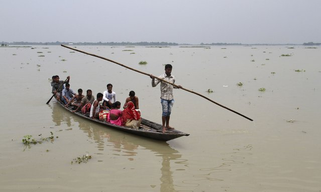 Villagers with their belongings move to safer places through the flooded areas of Morigaon district in the northeastern Indian state of Assam August 19, 2014. The latest heavy rains have caused landslides and floods in many parts of India and Nepal, where at least 90 people have been killed since Thursday. (Photo by Reuters/Stringer)