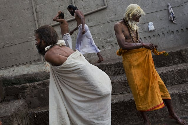 Hindu devotees dress after taking a bath in the Godavari River during Kumbh Mela, or Pitcher Festival, in Nasik, India, Saturday, August 29, 2015. (Photo by Bernat Armangue/AP Photo)