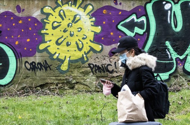 A woman walks by coronavirus graffiti, in Edinburgh, Scotland, Saturday March 21, 2020. For some people the COVID-19 coronavirus causes mild or moderate symptoms, but for others it causes severe illness. (Photo by Jane Barlow/PA Wire via AP Photo)