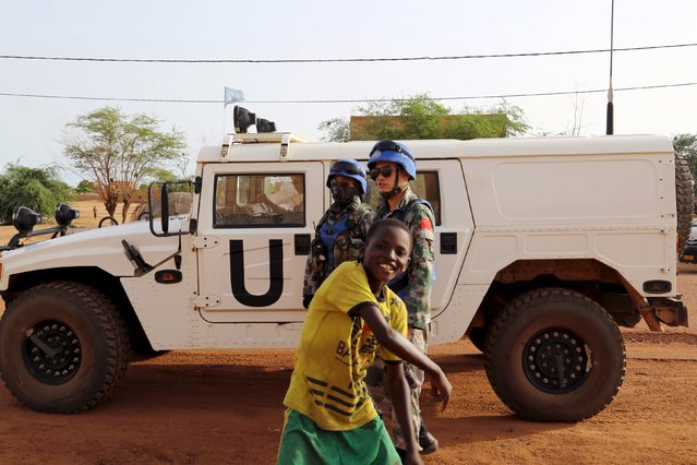 A boy dances in front of Chinese peacekeepers in Gao, Mali, August 11, 2015. The United Nations has deployed 10,000 peacekeepers and poured more than $1 billion into Mali but its efforts to end a three-year conflict are threatened by the reemergence of a centuries-old rivalry between Tuareg clans. (Photo by Emma Farge/Reuters)