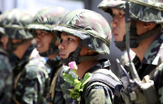 Thai soldier with a rose watches Thai anti-government protesters near downtown Monday, April 13, 2009, in Bangkok, Thailand. (Photo by Wong Maye-E/AP Photo)