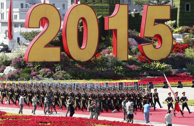 Soldiers of People's Liberation Army (PLA) of China walk past a sign of 2015 as they attend a flag-raising ceremony at the beginning of the military parade marking the 70th anniversary of the end of World War Two, in Beijing, China, September 3, 2015. (Photo by Reuters/China Daily)