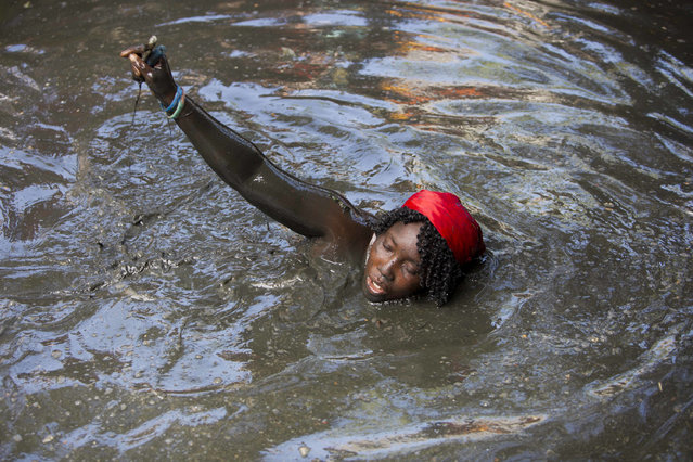 In this July 24, 2016 photo, a pilgrim takes a bath in a sacred mud pool during the annual Voodoo celebration in Plaine-du-Nord, Haiti, Saturday, July 23, 2016. Pilgrims come to bathe in the mud and make offerings expecting a miracle. (Photo by Dieu Nalio Chery/AP Photo)