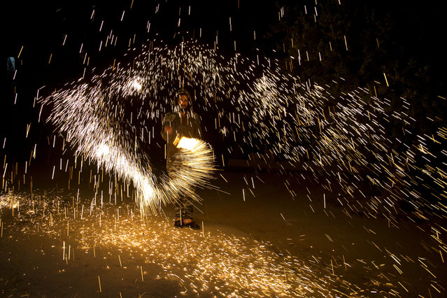 A Palestinian plays with fireworks as he celebrates the start of the Muslim holy month of Ramadan in the West Bank city of Nablus, Thursday, April. 23, 2020. (Photo by Majdi Mohammed/AP Photo)