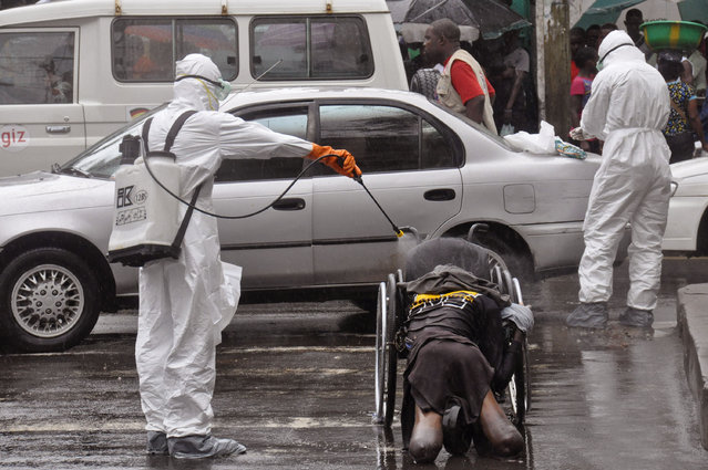 Health workers spray the body of a amputee suspected of dying from the Ebola virus with disinfectant, in a busy street in Monrovia, Liberia, Tuesday, September 2, 2014.  Food in countries hit by Ebola is getting more expensive and will become scarcer because many farmers won't be able to access fields, a U.N. food agency warned Tuesday.(Photo by Abbas Dulleh/AP Photo)