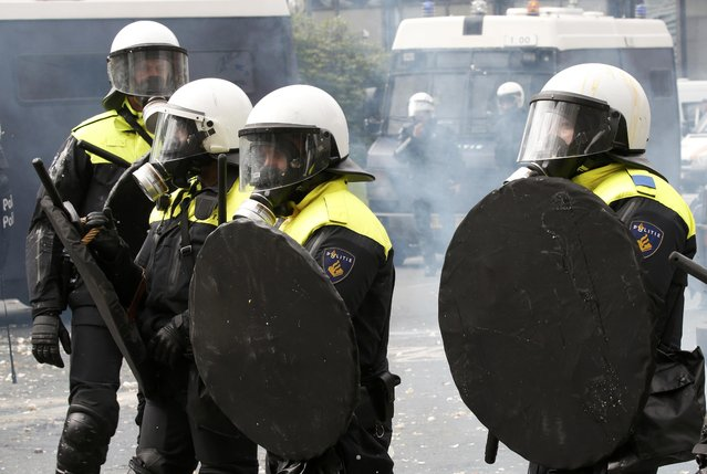 Belgian riot police officers shelter behind their shields while demonstrators throw eggs as farmers and dairy farmers from all over Europe take part in a demonstration outside an European Union farm ministers emergency meeting at the EU Council headquarters in Brussels, Belgium, September 7, 2015. (Photo by Jacky Naegelen/Reuters)