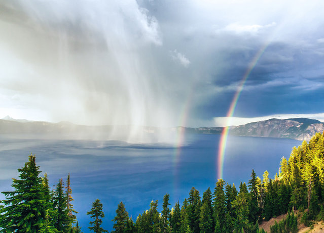 Crater Lake Storm at Sunset: A thunderstorm swirls across the water at Crater Lake National Park, as the setting sun creates a rare double rainbow. Taken from Rim Village, approximately 1,000 feet above the lake's surface, providing a straight-on vantage point of the storm. (Photo by Duke Miller/National Geographic Photo Contest