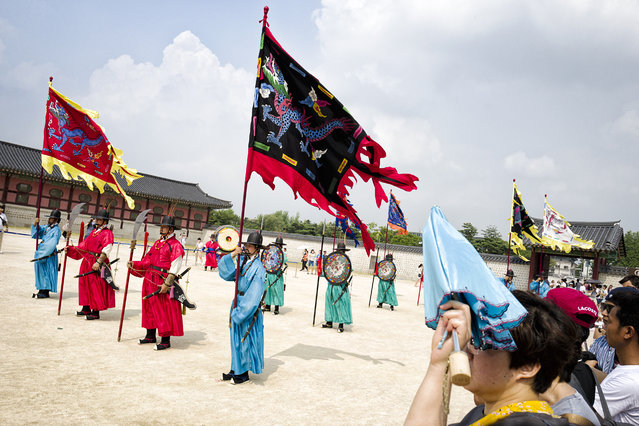 """Tourist watch Changing Sumunjang, the royal palace gate guard at Gyungbokgung Palace on August 1, 2015 in Seoul, South Korea. Gyungbokgung is the royal palace of Joseon Dynasty which was constructed in 1395. """"Gyungbok"""" means """"praying for the King, King's family and the nation"""" and """"gung"""" means """"a palace"""". (Photo by Shin Woong-jae/The Washington Post)"""