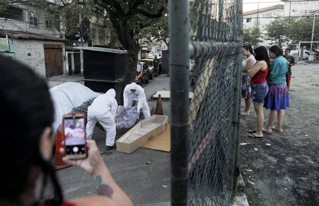 Workers of a funeral parlour, wearing protective clothing, remove the body of Valnir Mendes da Silva, 62, that was laying on a sidewalk of Arara community, where he died after residents requested help from the emergency service as he was suffering from breathing problems, during the coronavirus disease (COVID-19) outbreak, in Rio de Janeiro, Brazil, May 17, 2020. According to the residents, the body took about 30 hours to be removed. (Photo by Ricardo Moraes/Reuters)