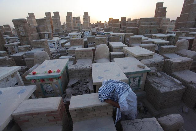 A man grieves at a cemetery in Najaf, south of Baghdad September 15, 2014. (Photo by Alaa Al-Marjani/Reuters)