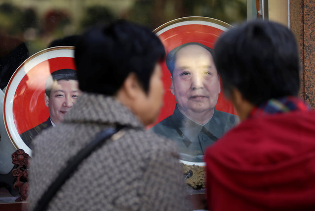 Tourists look at souvenir plates with images of Chinese late Chairman Mao Zedong (R) and Chinese President Xi Jinping outside a shop next to Tiananmen Square during the ongoing 19th National Congress of the Communist Party of China, in Beijing, China October 23, 2017. (Photo by Jason Lee/Reuters)