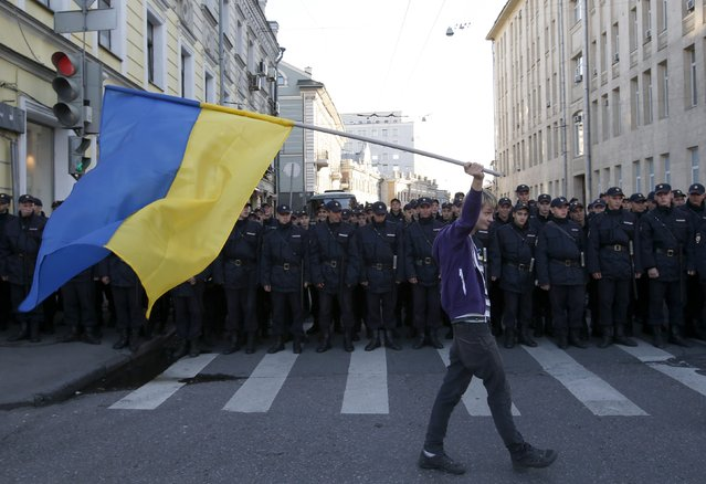 A man with a Ukrainian flag walks past riot police standing guard during an anti-war rally in Moscow, September 21, 2014. Thousands of Russians marched in protest against the armed conflict in Ukraine on Sunday in the first major anti-war rally since the start of the standoff between Kiev and pro-Russian rebels. (Photo by Maxim Zmeyev/Reuters)