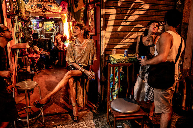 """Lapa, Rio de Janeiro. """"Lapa is one of the hot nightspots in Rio. This was at about 3am and we were catching a bus back to the beach, and I saw this bar next to the bus stop. My camera was in the bag. The night was over I thought. The light and the characters were so intriguing I just had to make a few frames"""". (Photo by David Alan Harvey/The Guardian)"""