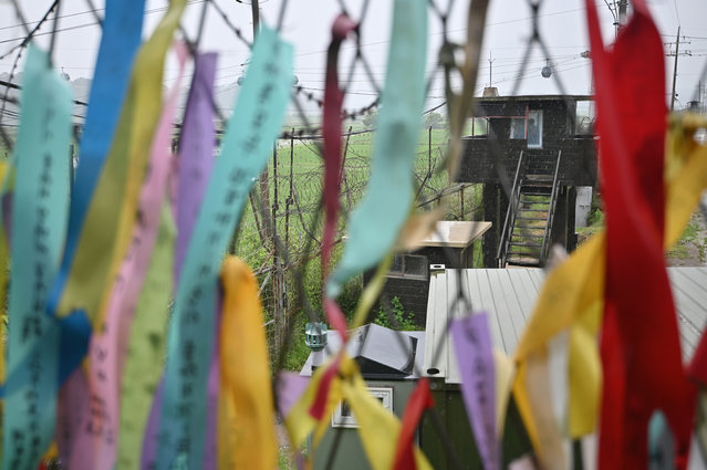 A South Korean guard post is seen through a military fence decorated with ribbons wishing for peace and reunification of the Korean Peninsula at Imjingak peace park in the border city of Paju on June 24, 2020. North Korean leader Kim Jong Un has suspended plans for military action against the South, state media reported on June 24 in an apparent sudden dialling-down of tensions after Pyongyang blew up a liaison office. (Photo by Jung Yeon-je/AFP Photo)