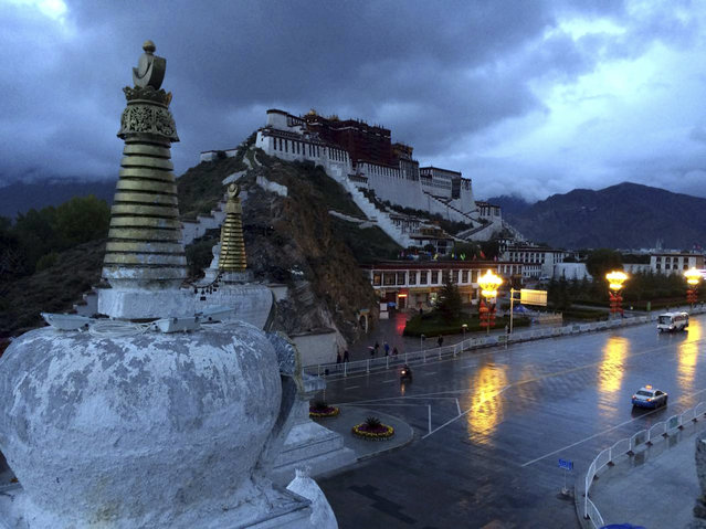 Pedestrians and vehicles make their way past the Potala Palace early on a rainy morning in Lhasa, capital of the Tibet Autonomous Region in China, Saturday, September 19, 2015. (Photo by Aritz Parra/AP Photo)