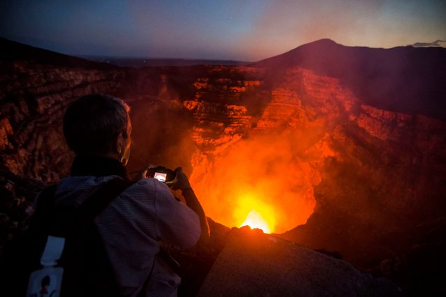 A tourist takes pictures of a lava lake inside the crater of the Masaya Volcano in Masaya, some 30km from Managua on May 19, 2016. Hundreds of tourists arrive daily to observe the lava flow which formed six months ago near the surface of the crater of the small Masaya volcano, one of the most active in Nicaragua. (Photo by Inti Ocon/AFP Photo)