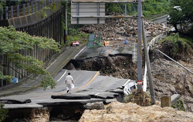 A man walks on heavily damaged road following a heavy rain in Kumamura, Kumamoto prefecture, southern Japan Monday, July 6, 2020. Rescue operations continued and rain threatened wider areas of the main island of Kyushu. (Photo by Koji Harada/Kyodo News via AP Photo)