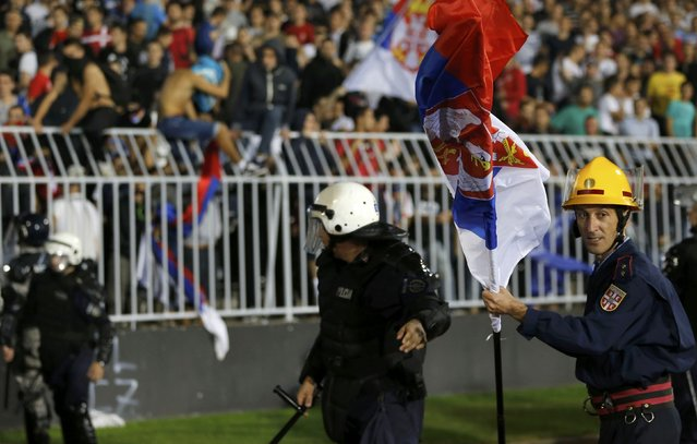 A firefighter carries a Serbian flag after it was thrown onto the pitch during the Euro 2016 Group I qualifying soccer match between Serbia and Albania at the FK Partizan stadium in Belgrade October 14, 2014. (Photo by Marko Djurica/Reuters)