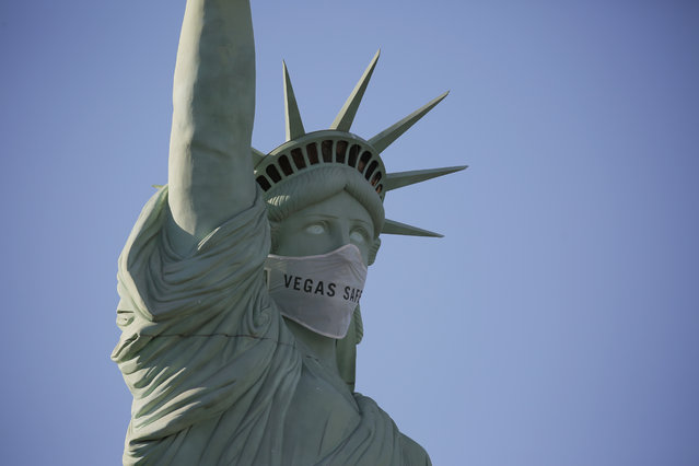 An oversized mask adorns the face of a replica Statue of Liberty at the New York-New York hotel and casino Thursday, July 16, 2020, in Las Vegas. MGM Resorts International has put a mask on the Statue of Liberty to remind people to wear a face covering as a precaution against coronavirus. (Photo by John Loche/AP Photor)