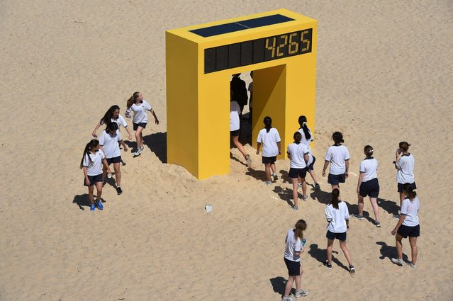 "Schoolchildren walk through the artwork ""Counter"" by Australian artist Geoffrey Drake-Brockman, who's solar powered artwork counts each time someone walks through it, part of a selection of artworks featured in the annual Sculpture by the Sea on the ocean walk between Bondi Beach and Tamarama Beach in Sydney, Australia, 23 October 2014. (Photo by Dean Lewins/EPA)"