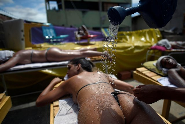 A woman is cooled down with a watering can as she sunbathes using insulating tape, at a beauty center in Belo Horizonte, Brazil, on December 21, 2017. (Photo by Douglas Magno/AFP Photo)