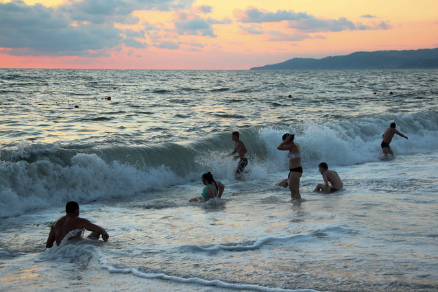 People bathe in the Black Sea during a storm in Sochi, Russia on July 21, 2020. (Photo by Dmitry Feoktistov/TASS)