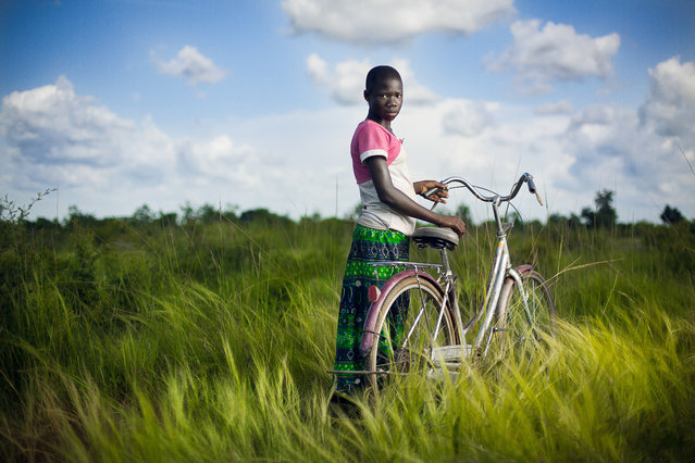"""Girl and her Bike"". We did not know how to communicate with each other. Everything called me to this photo. The sky. The grass. Her. Her bike. It was the perfect setting and I made a friend who gave me a photograph I will never forget taking. From my 2 week trip in Ghana. Photo location: Tamale, Ghana, Africa. (Photo and caption by Aaron Thomas/National Geographic Photo Contest)"