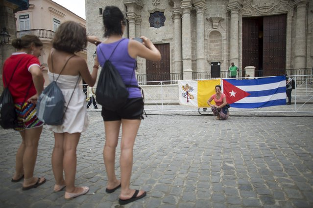 People take pictures with the Vatican (L) and Cuban flags in front of the The Cathedral of The Virgin Mary of the Immaculate Conception in Havana, September 18, 2015. (Photo by Alexandre Meneghini/Reuters)