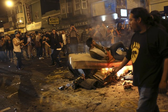 A man lays on a burning mattress set ablaze along the street in the Mission District during a celebration after the San Francisco Giants defeated the Kansas City Royals in Game 7 of the World Series, in San Francisco, California October 29, 2014. (Photo by Robert Galbraith/Reuters)