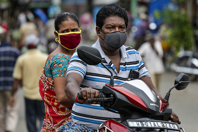 A couple wearing face masks as a precaution against the coronavirus travel on a two wheeler in Kolkata, India, Sunday, Aug. 2, 2020. India is the third hardest-hit country by the COVID-19 pandemic in the world after the United States and Brazil. (Photo by Bikas Das/AP Photo)
