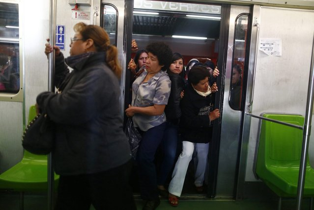 Women push open the sliding doors of a Women-Only passenger car in the subway in Mexico City October 24, 2014. Trains, buses and taxis for women only are on the rise in cities globally with a Thomson Reuters Foundation survey finding women feel safer on single-s*x transport but gender experts dismissing this as a band-aid solution that could backfire for women. (Photo by Edgard Garrido/Reuters)