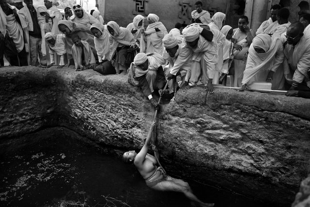 """""""Pilgrims gather to watch as an infertile worshiper is lowered into a baptism pool with a rope held by priests. According to local faith the holy water has fertility powers that will allow her to conceive. Every year, just before Christmas day, thousands of pious Christian orthodox worshipers make a pilgrimage to Lalibela, a small town in Ethiopia's highlands, known as Jerusalem of Africa or Black Jerusalem. Lalibela is famous for its 13th century monolithic churches, carved out of the living rock"""". (Photo and comment by Gali Tibbon, Israel/2013 Sony World Photography Awards"""