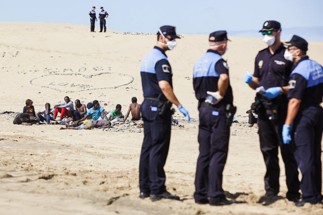 Would-be immigrants rest on Maspalomas beach next to policemen, on Gran Canaria in Spain's Canary Islands. (Photo by Borja Suarez/Reuters)