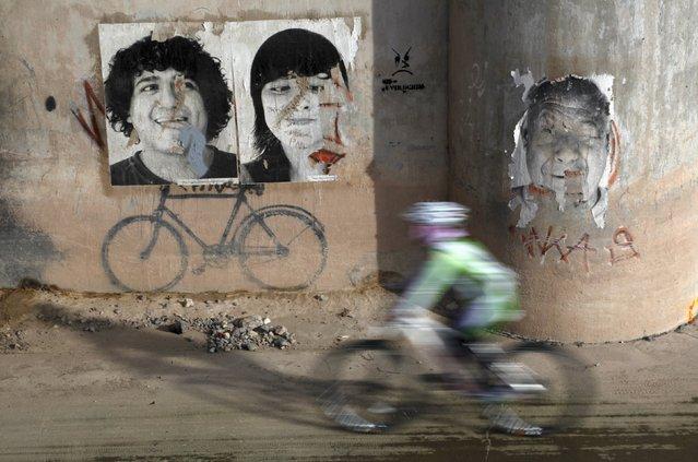A cyclist pedals past posters under a bridge connecting El Paso with Ciudad Juarez, Mexico, October 10, 2015. (Photo by Jose Luis Gonzalez/Reuters)