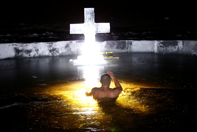 A man crosses himself as he dips in icy waters of a lake on the eve of Orthodox Epiphany in Minsk, Belarus on January 19, 2018. (Photo by Vasily Fedosenko/Reuters)
