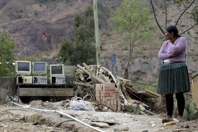 A woman stands next to computer waste in Vila Vila, south of Cochabamba, October 11, 2015. Bolivia is currently hosting the World People's Conference on Climate Change and the Defense of Life, which is held ahead of the Climate Change Conference in Paris. (Photo by David Mercado/Reuters)