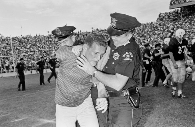 An unidentified Oklahoma fan is hustled off the playing field by two Dallas policeman in the last four seconds of play during the Oklahoma vs Texas football game in Dallas, October 13, 1962. The game almost erupted into a free-for-all fight just before the final whistle when members of both teams exchanged blows and spectators from both sides rushed onto the field. (Photo by Ferd Kaufman/AP Photo)
