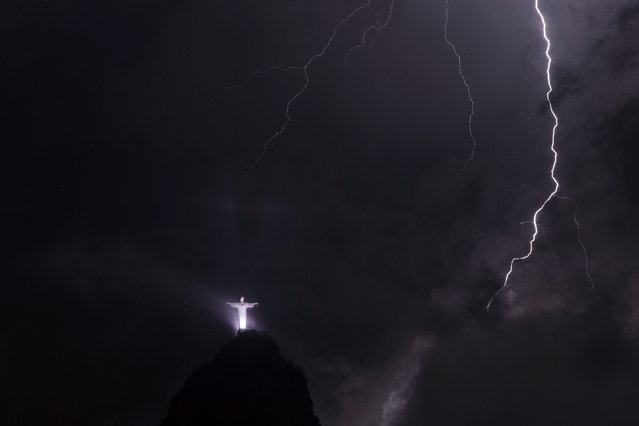 A lightning strikes in front of The Christ the Redeemer (Cristo Redentor) statue atop of Corcovado Mountain during a storm in Rio de Janeiro, Brazil, 23 February 2016. (Photo by Marcelo Sayao/EPA)