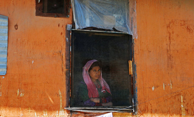 A woman looks out from a window during a protest against the recent killings in Kashmir, in Srinagar September 16, 2016. (Photo by Danish Ismail/Reuters)