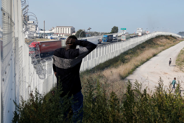 Migrant walks past the fence which secures the approach to the city from migrants trying to reach Britain, in Calais, France, September 21, 2016. (Photo by Pascal Rossignol/Reuters)